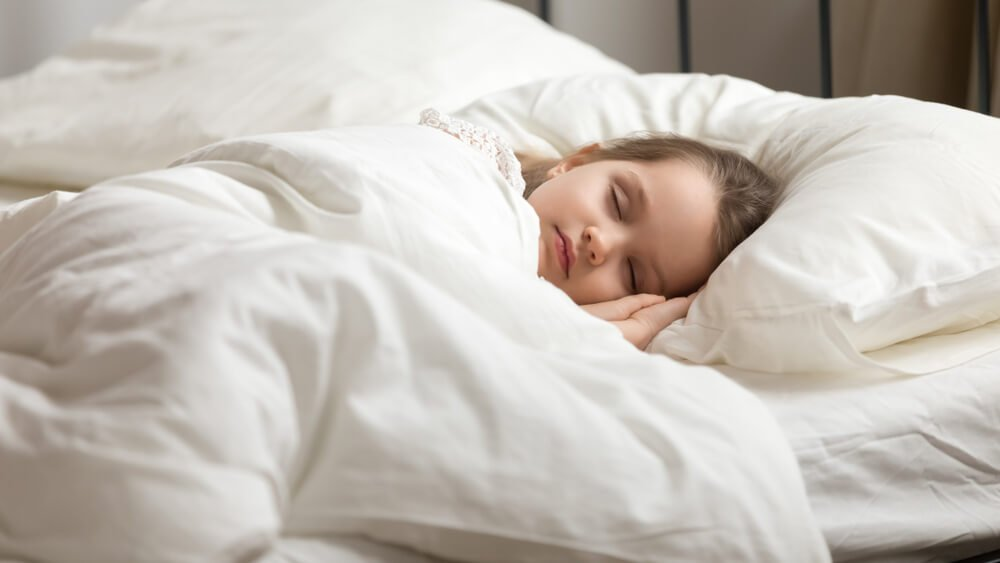 Tranquil preschool child girl covered with white fresh duvet lying in bed comfortable mattress By fizkes